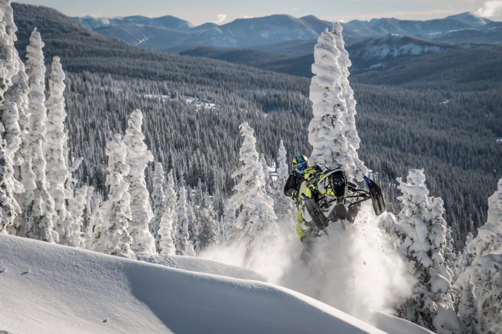 Snowmobile, or sled, getting air off a ridge feature.